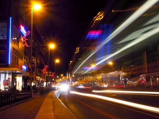 Vredenburg met avondverlichting en voorbij rijdend verkeer.