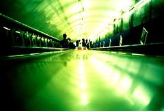 Slide! (fotobes) Tags: blue people green london film 35mm lights lca xpro geometry crossprocess tube angles slide londonunderground goingdown lomographychrome100 fotobes analogueescalator tunnelphilia