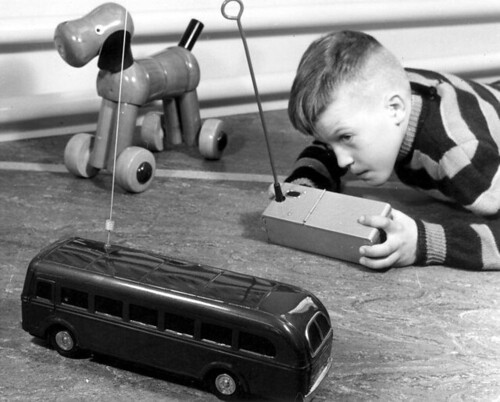 Jongetje speelt met radiografisch bestuurde speelgoedbus / Boy  playing with a radio-controlled toy bus
