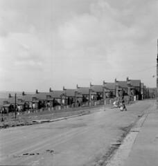 Sloping street (Tyne & Wear Archives & Museums) Tags: sky blackandwhite newcastle children landscape community sad terrace destruction bleak melancholy 1970s buggy desolate