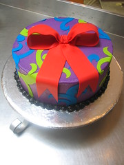 Wicked Chocolate cake iced in purple butter icing decorated with blue & lime green moulin rouge twirls & red puffy fondant bow (Charly's Bakery) Tags: birthday cake town tv chocolate wicked angels bakery reality cape charlys january2011