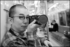 On our way to Tsukishima (Eric Flexyourhead) Tags: camera bw man guy slr japan train subway japanese tokyo blackwhite friend photographer metro bokeh dude riding 35mmfilm flannel   plaid rider koto kotoku canonf1   toeioedoline olympusep1 panasoniclumix20mmf17