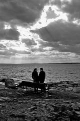 a moment (phototaxis) Tags: ocean light people bw beach clouds digital rocks dramatic nostalgic pointandshoot rays canonpowershota550