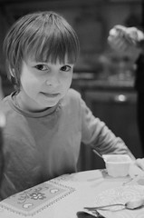 need moar youghurt (idea-saras) Tags: boy portrait blackandwhite bw kitchen face childhood night digital table evening eyes child russia bokeh meals grain tshirt spoon stare yoghurt yogurt noise glance dima