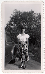 Woman Wearing Uniformed Hat (QueenofTarts) Tags: woman hat car photo costume uniform dress border skirt clothes 1950s era snapshots 50s scallop 1952 vintagephotos