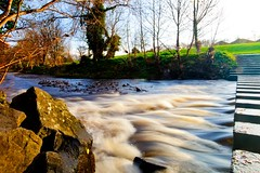 Rapids in slow motion (Steve-h) Tags: longexposure trees ireland dublin sun sunlight nature grass sunshine canon river lens concrete rocks shadows stones tripod ivy wideangle rapids steppingstones riverbank bushypark lightweight dodder mirrorlockup iso50 steveh riverdodder canonef1635mmf28liiusm velbontripod canoneos5dmkii canoneos5dmk2 doubleniceshot tripleniceshot mygearandme mygearandmepremium mygearandmebronze mygearandmesilver mygearandmegold mygearandmeplatinum mygearandmediamond wirelessremotecontrolshutterrelease