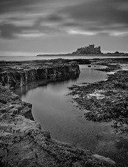 Bamburgh Castle (Boyd Hunt) Tags: longexposure sea bw cliff seaweed castle beach clouds island mono rocks ruin rockpool