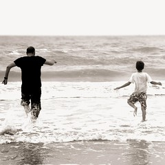 Father and Son [O] (Skipology) Tags: sea people blackandwhite bw seascape cold beach water monochrome canon square blackwhite candid father norfolk son run splash dslr 60d 18mm135mm eos60d