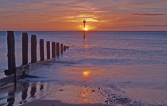 Teignmouth Sunrise (Jason Way (JW Images)) Tags: ocean blue sea orange sun seascape water silhouette clouds reflections blackwhite sand nikon waves glow shadows tide pebbles devon posts breakwater teignmouth d40x