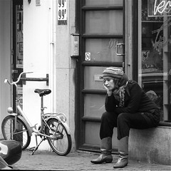 In Thoughts... (Akbar Simonse) Tags: street people urban bw woman holland netherlands girl monochrome bicycle square waiting boots zwartwit candid streetphotography denhaag cap thehague fiets foldingbicycle streetshot straat noordeinde vouwfiets straatfotografie straatfoto straatfotograaf dedoka nederlandvandaag akbarsimonse