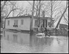 Man wades past cottage, New England flood (Boston Public Library) Tags: weather storms floods lesliejones