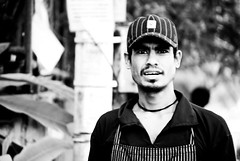 Portrait of a Stranger #4 : The Guy Working At  The Caf (Anant N S (www.thelensor.tumblr.com)) Tags: anantns thelensor pune india photography nikon d3000 nikkor 55200 project365 day146 day15 artisticphotography art cool awesome amazing unbelievable conceptual portrait streetphotography street theguyworkingatthecaf portraitofastranger stranger streetportraiture guy man worker apron cap beard grumpy headshot blackandwhite monochrome bw