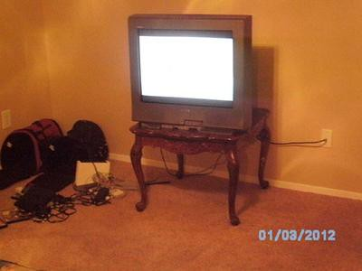A TV that I bought, sitting on a table that my big sister bought