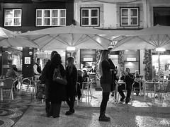 Phone Convo (weizor) Tags: city windows portrait blackandwhite bw woman portugal night lumix cafe europe cityscape chairs lisbon streetphotography panasonic cobblestones phonecall umbrellas micro43 microfourthirds 20mmf17asph dmcg3