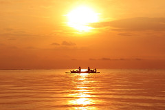 THE  FISHERMAN ON DUTY,, (ManButur PHOTOGRAPHY) Tags: morning light sea sky bali sun reflection beach nature water sunrise canon indonesia landscape photography eos boat agua scenery aqua asia glow sigma human activity 18200mm sillhuette 450d pantaikarang