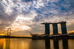 Sunrise with fluffy clouds over the Singapore flyer and MBS (jh_tan84) Tags: longexposure blue orange sun water clouds marina sunrise river landscape bay singapore fluffy mbs singaporeflyer marinabaysands