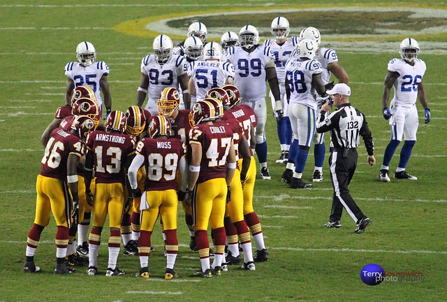 Redskins QB DONOVAN MCNABB sets play in huddle.