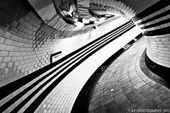 Go Faster Stripes (Aaron Yeoman) Tags: lighting city uk greatbritain travel light england urban blackandwhite bw reflection london lines station sign architecture reflections underground subway tile lights blackwhite europe arch bend metro unitedkingdom sony curves perspective railway tunnel line tiles gb tubestation londonunderground subwaystation alpha curve vignetting vignette thetube metrostation northernline tfl lul theunderground undergroundstation rapidtransit a700 hampsteadundergroundstation fluorescentlamp metropolitanrailway fluorescentlamps tamronspaf1750mmf28xrdiii hampsteadtubestation sonyalpha700 dslra700