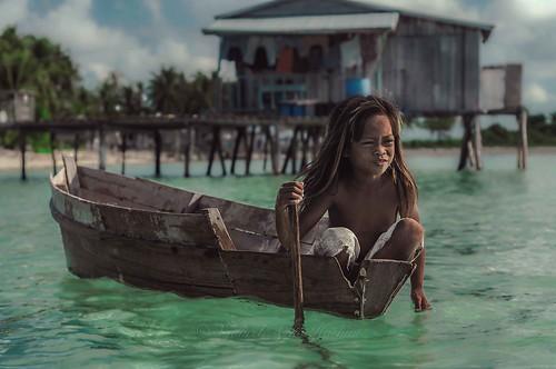 Little girl paddling a wooden boat.
