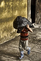 morning chores (Pejasar) Tags: boy carry garbage trash blueboots child work morning