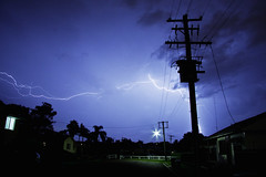 Passing Storm (Leighton Wallis) Tags: houses homes storm clouds fence streetlight fork bolt lightning powerpole thunder