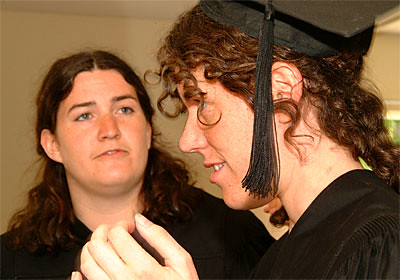 Graduates Lori Bennett and Sarah Cohen Contemplate Mortarboard Placement.