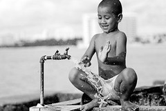 Art_in_All_of_Us_-__D201225-bw (anthonyasael) Tags: ocean life street city boy sea portrait usa brown haircut playing black blur game building public water smile face look smiling dark island drops kid spring healthy hands child play hand pacific skin drink bare chest unitedstatesofamerica small young bald drinking hairdo ground running drop spray clean health wash hide abroad short barefoot droplet shorts straight splash tap hiding washing source guam throw territory nip rinse sip polynesian spatter splashing skinned oceania spattering splasher