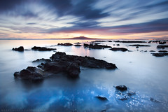 Dawn of Rangitoto (Mark Emirali) Tags: ocean longexposure blue light sea newzealand sky cloud seascape blur colour art nature clouds canon landscape rocks mood auckland northshore nz canon5d milford aotearoa takapuna eastcoast rangitoto copyrighted 1740f4l gndfilter pleasedonotusewithoutmypermission 5dmkii markemirali markemiraliphotography