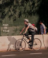 Man and Shadow Biking On Essex Street Manhattan (nrhodesphotos(the_eye_of_the_moment)) Tags: dsc0466272 theeyeofthemoment21gmailcom wwwflickrcomphotostheeyeofthemoment essexstreet shadows reflections biker bike man people barrier street streetscene les biking signs concrete pavement spokes wheels helmet outdoor vehicle tranportation