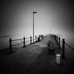 Promenade (Andy Brown (mrbuk1)) Tags: longexposure bw mist seascape lines fog fence reflections dark bench square boats mono pier blackwhite mood harbour grain perspective atmosphere lamppost devon fade posts torquay tone diagonals neutraldensity englishriviera departurepointc