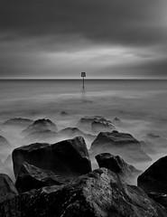 Last Man Standing (Richard Hookway) Tags: ocean uk sea england bw seascape clouds rocks moody haylingisland dramatic wave hampshire slowshutter coastline seadefence weldingglass milkywater canon40d 12shade
