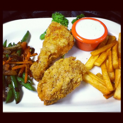 Pan fried chicken with French fries and sautéed green beans, carrots and tomatoes