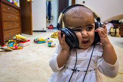 Musical prodigy (modenadude) Tags: baby color cute girl face field kids canon toys back toddler funny raw dof child floor bokeh muslim humor young large adorable tokina laugh headphones pakistani karachi clifton depth f28 squished aisha oversize scrunched 1116 t2i lightroom4