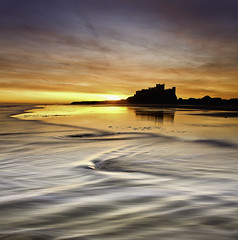 Bamburgh Castle - Morning Waves (Tired but Willin) Tags: morning sea sky sun seascape motion castle beach water clouds sunrise bay coast early seaside sand waves colours northumberland workshop bamburghcastle tonyspencer dougchinnery