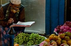 Counting Grapes? (Pagan Eyes) Tags: street orange man apple fruits fruit night book nightshot candid streetphotography bd grape bangladesh seller fruitseller chittagong dampara countinggrapes