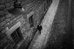 Urban Prey.. (Peter Levi) Tags: street city blackandwhite bw woman blancoynegro lamp architecture streetlight sweden stockholm streetphotography cobblestones blackwhitephotos