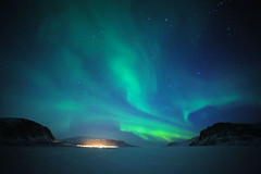 The Night Lights of Pangnirtung, Nunavut (MichaelHD ( michaelhdavies.com )) Tags: ocean light snow mountains cold colour night stars landscape island lights star michael town nikon hill arctic aurora fjord ribbon nikkor northern nunavut isolated davies snowmobile borealis pangnirtung baffin d700 mountduval visipix michaelhdavies httpwwwflickrcomphotosmichaelhdavies6987433103inpool392839n22
