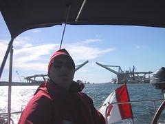 Leaving Port Vell (DJ Greer) Tags: barcelona winter red hat sunglasses sailboat port marina outside outdoors spain mediterranean sailing outdoor flag sail steer vell