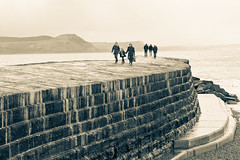 Promenading on the Cobb (Keith in Exeter) Tags: uk sea england people bw english wall mono coast seaside rocks exposure harbour artificial cliffs coastal promenade dorset cobb historical protection jurassic lymeregis breakwater goldencap handinhand filmlocation lymebay stonebarrow mygearandme mygearandmepremium frenchlieutenantswoman infinitexposure