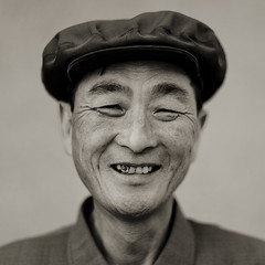 CHEF DU VILLAGE JUNG PYONG RI SOURIANT, COREE DU NORD (Eric Lafforgue Photography) Tags: people blackandwhite man male tourism smile face closeup square person asia noiretblanc head joy happiness korea headshot tourists communism asie coree sourire bonheur personne humanbeing joie communisme hosting homme tete northkorea tourisme visage grosplan dprk accueil carre touristes lookingatcamera blackandwhitepicture squarepicture loger democraticpeoplesrepublicofkorea accueillir etrehumain coreedunord rpdc regardantlobjectif northhamgyongprovince chilbosea republiquepopulairedemocratiquedecoree chilboarea merchilbo regiondechilbo myongchoncounty jungpyongrivillage imagecaree