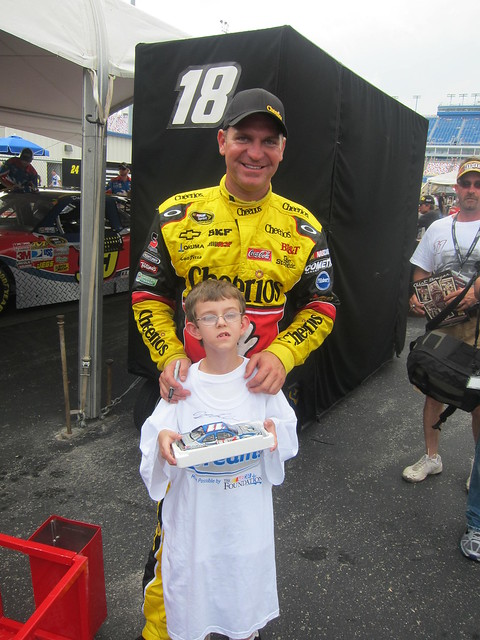 Clint Bowyer poses with a NASCAR Dreams child at the track