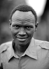 Policemean from the Nuer tribe with scarifications on the forehead, Gambella province, Ethiopia (Eric Lafforgue) Tags: africa people blackandwhite man male smile face look smiling vertical horizontal outside outdoors person artistic noiretblanc decorative portait joy decoration headshot front ornament bodypainting ethiopia forehead rite scar cicatrice sourire bonheur personne humanbeing joie scarification homme tete visage hapiness regard contemplation adornment afrique pigments dehors eastafrica abyssinia ethiopie sourir exterieur lookingatcamera nuer blackandwhitepicture 4614 abyssinie vueexterieure gambela gambella afriquedelest nomadicpeople etrehumain photoennoiretblanc regardantlobjectif peoplesoftheomovalley gambellaprovince provincedegambella regiondegambela gambelaarea nuertribe tribudesnuer