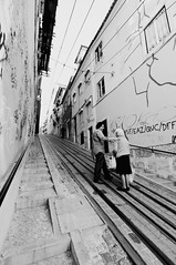 Helping hand (t3mujin) Tags: street old bw woman man lines lisbon perspective slope steep