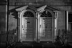 opposing doors (Daz Smith) Tags: city uk portrait people urban blackandwhite bw streets blancoynegro monochrome bicycle canon blackwhite bath doors candid citylife thecity streetphotography bikes ornate canon6d dazsmith bathstreetphotography