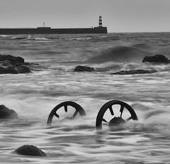 Waves Over Wheels (Adam_Duckett) Tags: uk longexposure sea motion industry beach landscape blackwhite movement rocks exposure squareformat