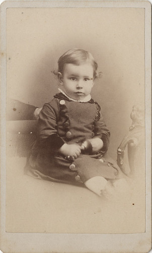 A Baby Boy With Large Buttons And A Hidden Mother Carte De
