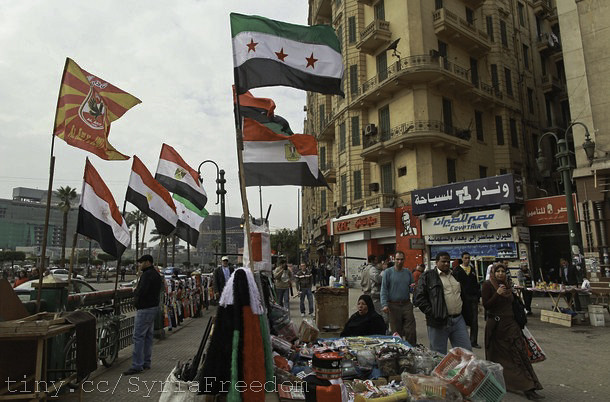 People walk past Syrian and Egyptian flags in Tahrir square in Cairo February 19, 2012.