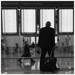 Departures (It's Stefan) Tags: blackandwhite man monochrome walking airport dubai emirates traveling departures indicador annunciatorpanel flightinformation