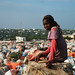 Young girl sits at the top of a hill overlooking Darwiish camp