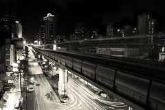 Sukhumvit by Night (Xavier Cloitre) Tags: city sky bw white black building cars blanco by night train point thailand nikon asia noir skyscrapers traffic y bangkok negro ciudad nb bn asie d200 skytrain vanishing et blanc ville bts thailande sukhumvit totallythailand xaviercloitre perscpectives